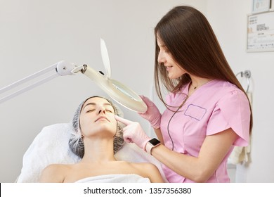Beautiful brunette woman undergoing medical examination, being examined by cosmetologist before having injection. Beautician expert examines cliants face under lamp before anty aging procedure.