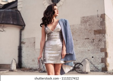 Beautiful brunette woman walking in the city ,wearing glitter dress and blue coat. Fashion spring summer photo