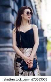 Beautiful brunette woman walking down the city street. Beauty, fashion outdoor.