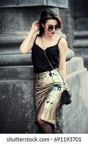 Beautiful brunette woman walking down the city street. Beauty, fashion outdoor.