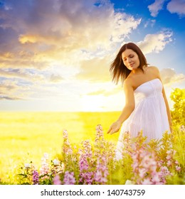 beautiful brunette woman walking in a field at sunset and touching flowers