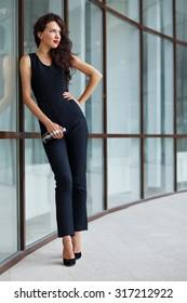 Beautiful brunette woman wearing black jumpsuit posing near the office building. Street fashion.