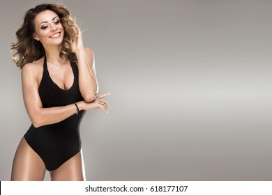 Beautiful brunette woman wearing black fashionable lingerie, studio shot.