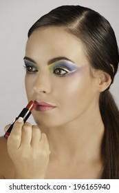 Beautiful brunette woman wearing colorful makeup applying red lipstick