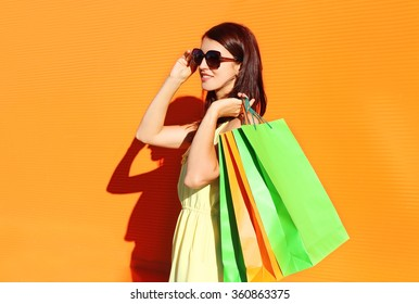 96f526664 Beautiful brunette woman wearing a dress with shopping bags in city