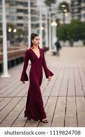Beautiful brunette woman wearing an elegant dress and walking in the city
