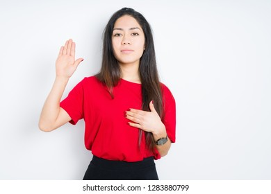 Beautiful brunette woman wearing red t-shirt over isolated background Swearing with hand on chest and open palm, making a loyalty promise oath