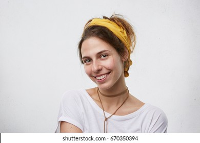 Beautiful brunette woman wearing yellow scarf on head, pendant on neck and white T-shirt smiling pleasantly into camera having eyes full of happiness. Cute female isolated over blank white wall