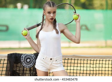 Beautiful brunette woman in white playing tennis outdoors in the morning on a clay court.