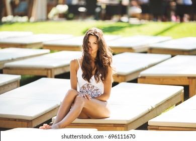 Beautiful brunette woman in a white swimsuit  is sunning on a white chaise longue.