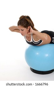 Beautiful brunette woman working out using an exercise ball.  Shot isolated on white background.