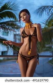 Beautiful brunette woman in yellow and black crochet bikini looking aside while standing on the balcony over tropical palm trees background