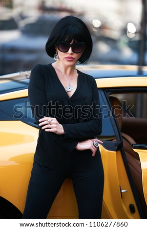 Beautiful brunette woman with yellow sport car. Young woman with dark hair  in black bodysuit and sunglasses posing near supercar - Image 6228d09ce
