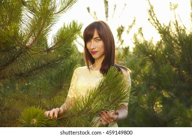 beautiful brunette in a yellow lace dress in the sunshine among the green trees