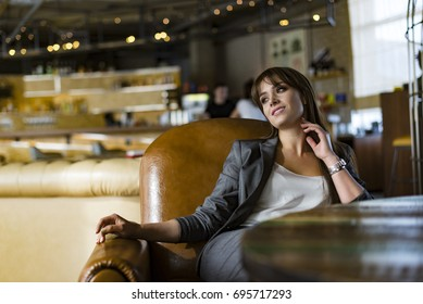 Beautiful brunette young woman in cafe. Summer time. Day light. Business woman. Lifestyle.