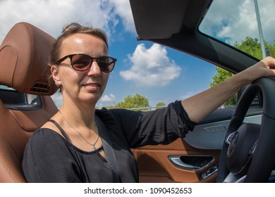 Beautiful Brunette Young Woman Driving a sports convertible  Car