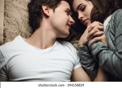 beautiful brunette young woman and guy lying in bed and holding tightly hands. The concept of tenderness and affection