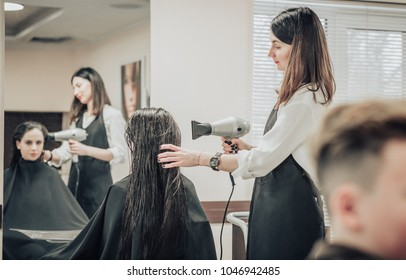 Beautiful brunette young woman at the hairdresser salon. Hairdresser making hairstyle.