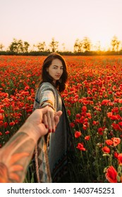 Beautiful brunette young woman holding male hand and leading him in poppy flower meadow at summer sunset, looking at camera. Point of view.