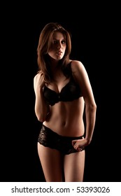 Beautiful brunette young woman with lace lingerie isolated on black