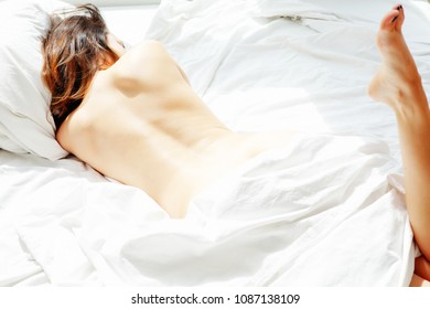 beautiful brunette young woman lying in bed with white bedsheets