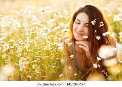 Beautiful brunette young woman lying in daisy field. Carefree happy cute woman with healthy curly hair having fun in chamomile field. Natural beauty. Harmony and freedom concept.