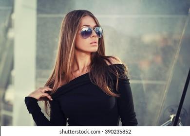 Beautiful brunette young woman in nice black dress, sunglasses. Fashion Photo