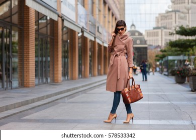 Beautiful brunette young woman in nice brown beige coat, jeans and sunglasses. High heels shoes. Spring fashion photo on urban background.
