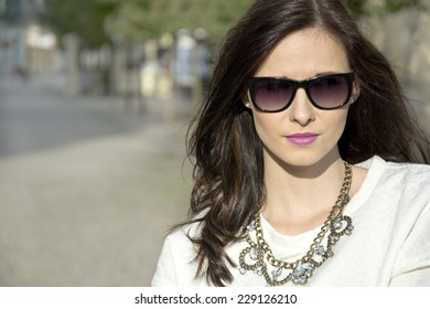 Beautiful brunette young woman with sunglasses and necklace on the street.