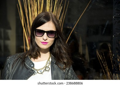 Beautiful brunette young woman with sunglasses on the street.