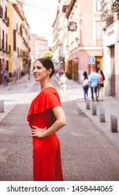 Beautiful brunette young woman with topknot hairstyle smiling and wearing red ruffles dress walking on the street. Fashion photo.