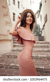 Beautiful brunette young woman wearing pink dress and straw hat walking on the street in old european Town. Fashion and style. Summer travel