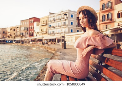 Beautiful brunette young woman wearing pink dress and straw hat enjoying sunrise on seafront in old european town. Fashion and style. Summer travel