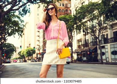 Beautiful brunette young woman wearing nice skirt and pink blouse, yellow purse, walking on the street. Fashion city photo