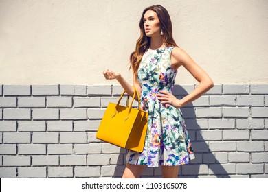 Beautiful brunette young woman wearing nice dress, yellow handbag, walking on the street. Fashion city photo. Flower pattern