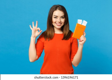 Beautiful brunette young woman wearing red orange dress hol in hand passport tickets isolated over trendy blue wall background, studio portrait. People lifestyle fashion concept. Mock up copy space