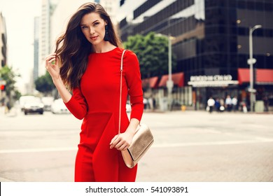 Beautiful brunette young woman wearing red dress, golden purse, walking on the street. Fashion photo