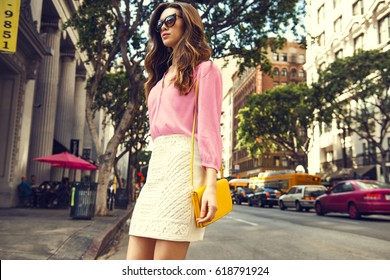 Beautiful brunette young woman wearing nice skirt and pink blouse, yellow purse, walking on the street. Fashion city photo