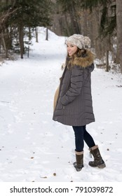 Beautiful brunette young woman in winter scene - snow covered park wearing winter clothes - parka with knit cap - standing on snow covered trail looking back over shoulder