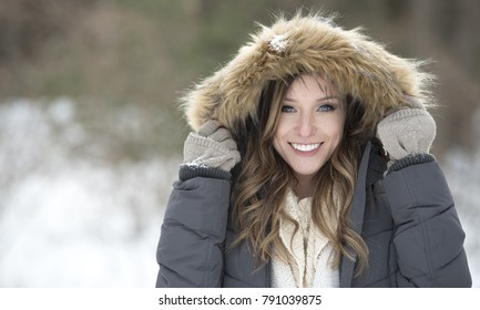 Beautiful brunette young woman in winter scene - snow covered park wearing winter clothes - layered sweaters and mittens holding park hood