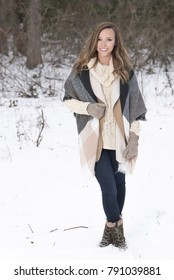 Beautiful brunette young woman in winter scene - snow covered park wearing winter clothes - layered sweaters and mittens