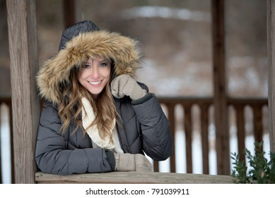 Beautiful brunette young woman in winter scene - snow covered park wearing winter clothes - layered sweaters and parka standing in gazebo or shelter