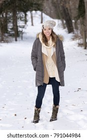 Beautiful brunette young woman in winter scene - snow covered park wearing winter clothes - parka with knit cap - standing on snow covered trail
