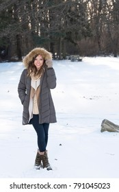 Beautiful brunette young woman in winter scene - snow covered park wearing winter clothes - parka with hood up, jeans, and boots