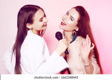 Beautiful brunettes on a pink background sing into a microphone. Teenager in karaoke. Girl with bright green make-up, earrings and red lips. Sisters on a pink background.