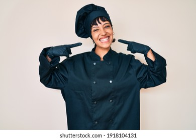 Beautiful brunettte woman wearing professional cook uniform smiling cheerful showing and pointing with fingers teeth and mouth. dental health concept.