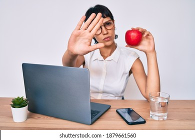 Beautiful brunettte woman working at the office eating healthy apple with open hand doing stop sign with serious and confident expression, defense gesture