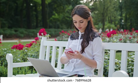 Beautiful brunnette lady sitting on a white bench in the park and using a laptop and a telephone. Medium shot
