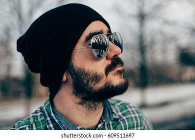 Beautiful brutal bearded man in a plaid shirt in the woods