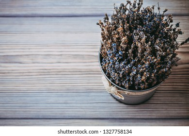 a beautiful bucket of dried lavender flowers on a wooden floor